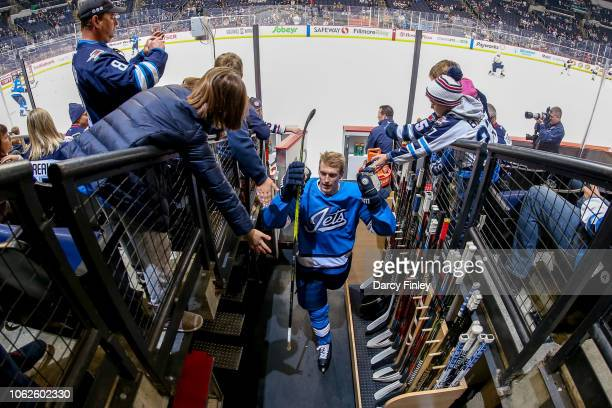 Tyler Myers of the Winnipeg Jets fist bumps fans as he leaves the ice following the pregame warm up prior to NHL action against the Buffalo Sabres at...