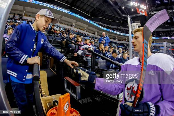 Tyler Myers of the Winnipeg Jets gives a puck to a young fan during the pregame warm up prior to NHL action against the Chicago Blackhawks on Hockey...