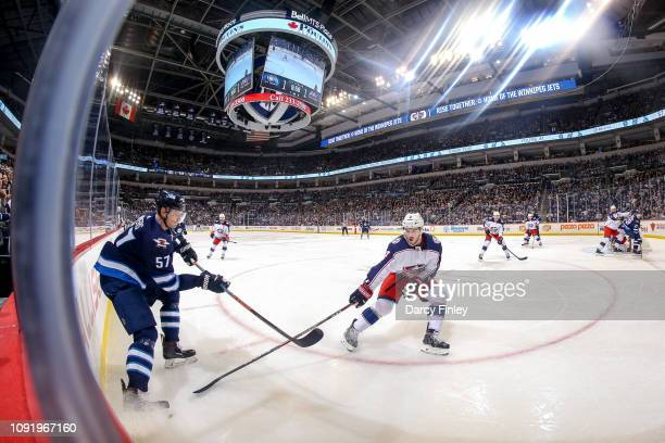 Tyler Myers of the Winnipeg Jets passes the puck as Scott Harrington of the Columbus Blue Jackets defends during first period action at the Bell MTS...