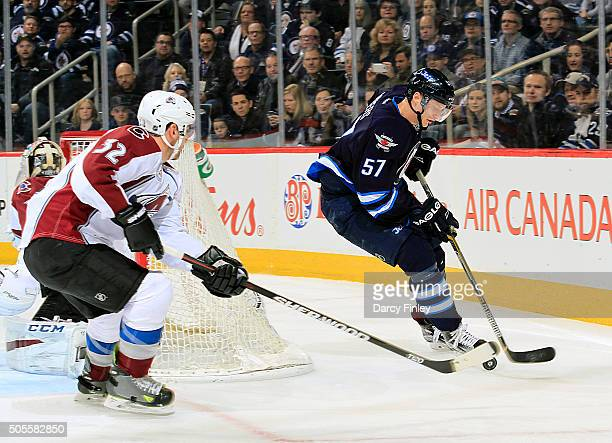 Tyler Myers of the Winnipeg Jets plays the puck around the net as Francois Beauchemin of the Colorado Avalanche defends during first period action at...