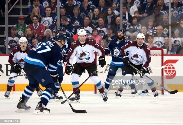 Tyler Myers of the Winnipeg Jets plays the puck at the point as JT Compher and Patrik Nemeth of the Colorado Avalanche defend during third period...