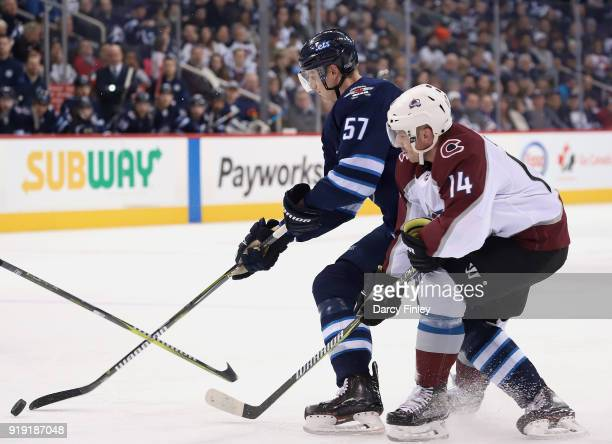 Tyler Myers of the Winnipeg Jets plays the puck away from Blake Comeau of the Colorado Avalanche during first period action at the Bell MTS Place on...