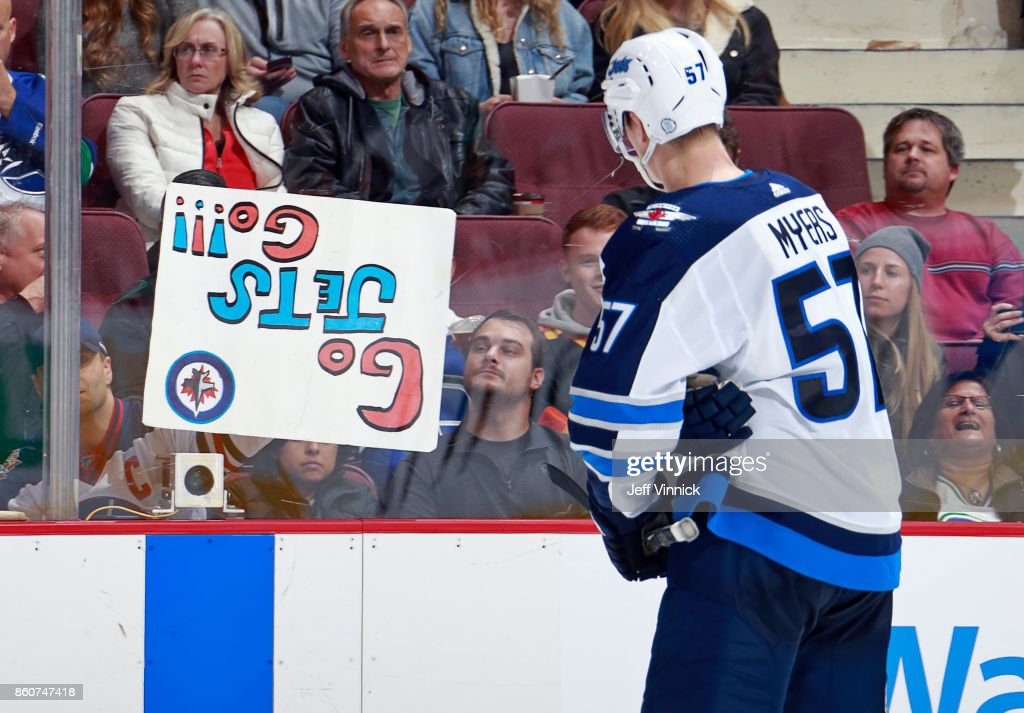 Tyler Myers #57 of the Winnipeg Jets skates over to tell fan to turn sign right side up during their NHL game against the Vancouver Canucks at Rogers Arena October 12, 2017 in Vancouver, British Columbia, Canada. The final score was 4-2 for the Winnipeg Jets.