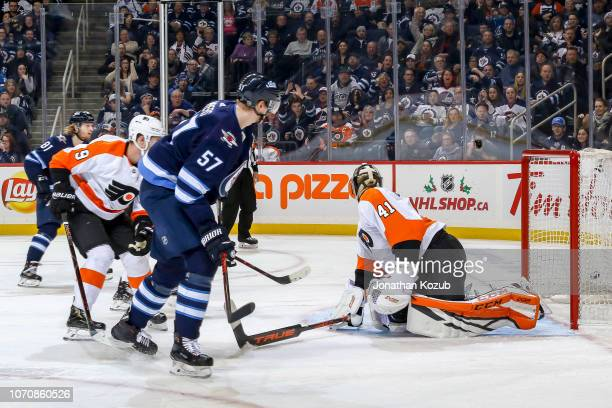 Tyler Myers of the Winnipeg Jets watches as the puck gets behind goaltender Anthony Stolarz of the Philadelphia Flyers for a third period goal at the...