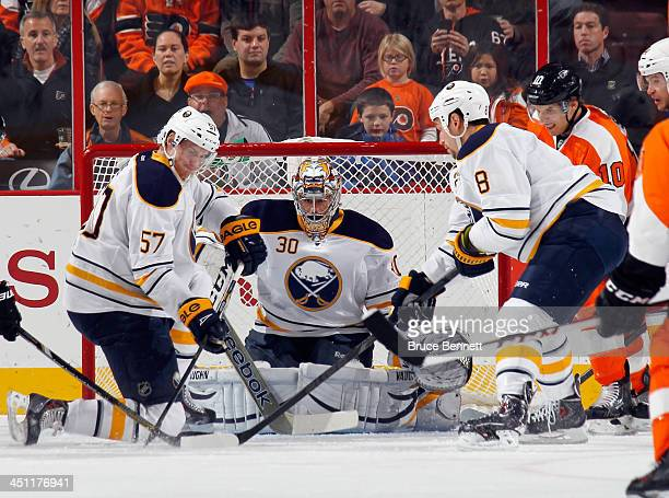 Tyler Myers Ryan Miller and Cody McCormick of the Buffalo Sabres defend the net against Brayden Schenn of the Philadelphia Flyers during the first...
