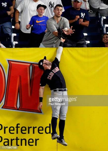 Tyler Naquin of the Cleveland Indians can't field a home run by Gleyber Torres as a fan reaches to catch it during the 8th inning in an MLB baseball...