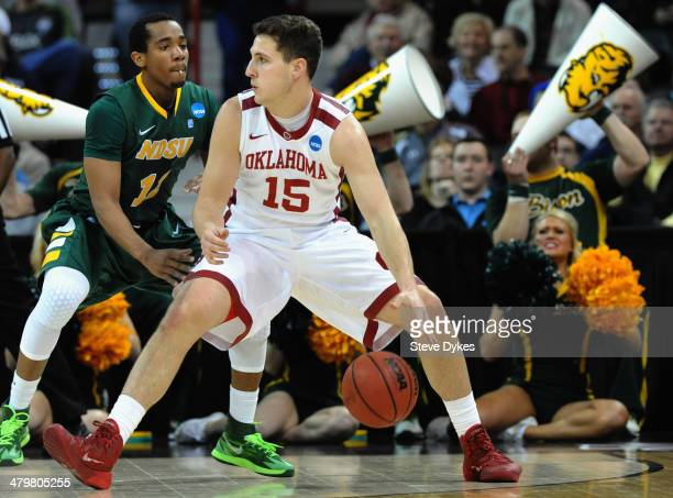 Tyler Neal of the Oklahoma Sooners dribbles against Lawrence Alexander of the North Dakota State Bison during the second round of the 2014 NCAA Men's...