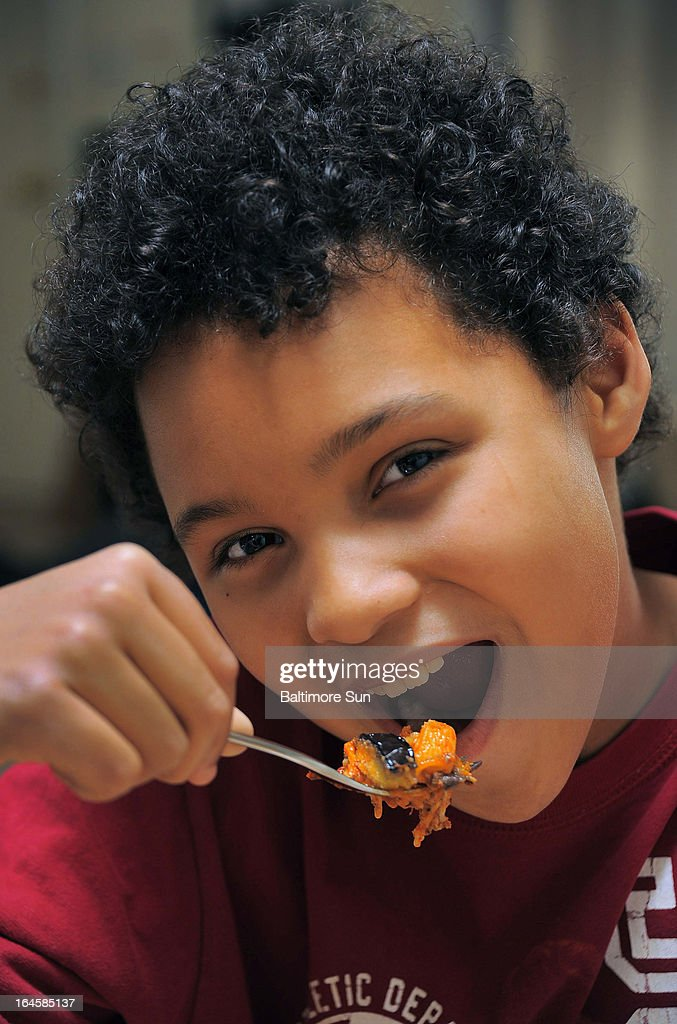 Tyler Parker-Rollins, 11, poses with a bite of the eggplant meal his mother made at their Lutherville-Timonium, Maryland home, March 7, 2013.