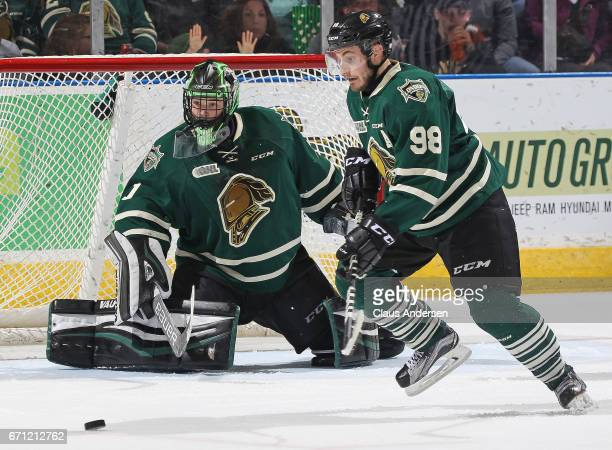 Tyler Parsons and Victor Mete of the London Knights keep their eyes on a loose puck against the Erie Otters in Game Six of the OHL Western Conference...