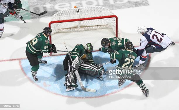 Tyler Parsons of the London Knights covers up a puck against Logan Brown of the Windsor Spitfires during Game Two of the OHL Western Conference...