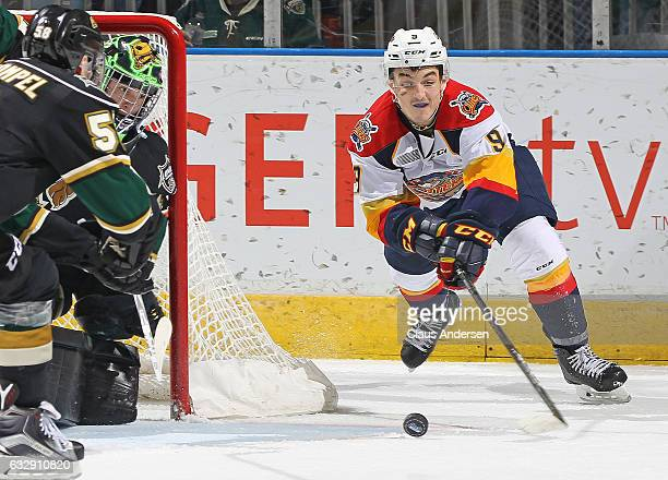 Tyler Parsons of the London Knights keeps tight to the corner against a scoring attempt by Kyle Maksimovich of the Erie Otters during an OHL game at...