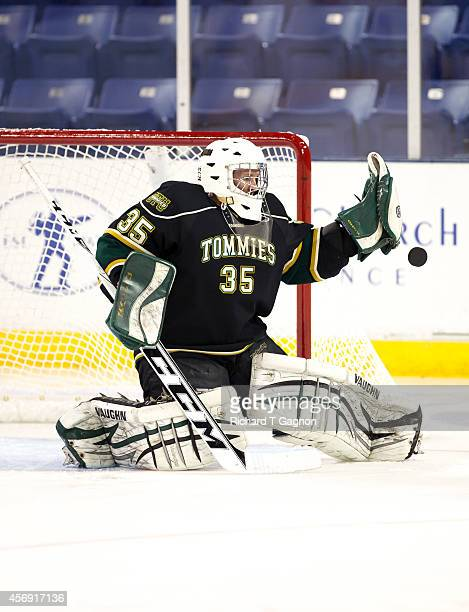 Tyler Piercy of the St. Thomas University Tommies makes a save before NCAA exhibition hockey against the Massachusetts Lowell River Hawks at the...