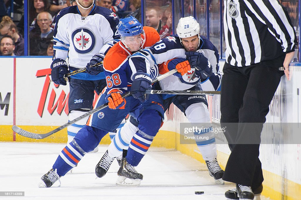 Tyler Pitlick #68 of the Edmonton Oilers battles for the puck against Patrice Cormier #28 of the Winnipeg Jets during a preseason NHL game at Rexall Place on September 23, 2013 in Edmonton, Alberta, Canada.