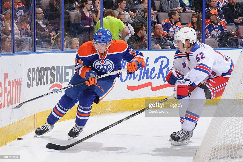 Tyler Pitlick #68 of the Edmonton Oilers skates with the puck against Tommy Hughes #52 of the New York Rangers during a preseason NHL game at Rexall Place on September 24, 2013 in Edmonton, Alberta, Canada.