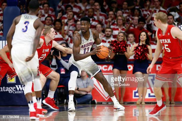 Tyler Rawson of the Utah Utes defends Deandre Ayton of the Arizona Wildcats during the first half of the college basketball game at McKale Center on...