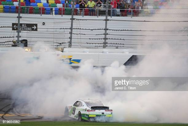 Tyler Reddick driver of the BurgerFi Chevrolet celebrates with a burnout after winning the NASCAR Xfinity Series PowerShares QQQ 300 at Daytona...