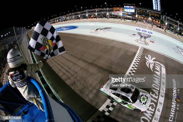 Tyler Reddick driver of the BurgerFi Chevrolet crosses the finish line to win the NASCAR Xfinity Series Ford EcoBoost 300 and the NASCAR Xfinity...