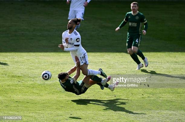 Tyler Roberts of Leeds United is tackled by George Baldock of Sheffield United during the Premier League match between Leeds United and Sheffield...