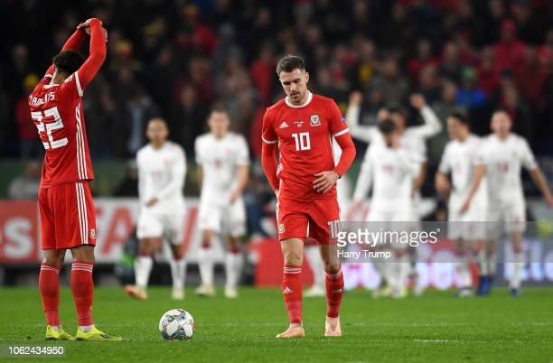 Tyler Roberts of Wales and Aaron Ramsey of Wales react as the Denmark team celebrate there first goal during the UEFA Nations League Group B match...