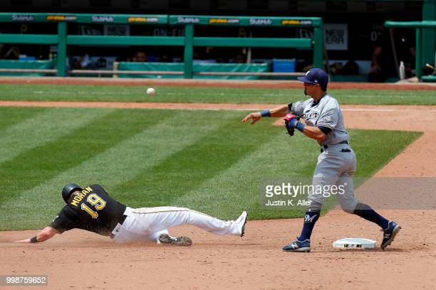 Tyler Saladino of the Milwaukee Brewers attempts to turn a double play against Colin Moran of the Pittsburgh Pirates in the sixth inning during game...