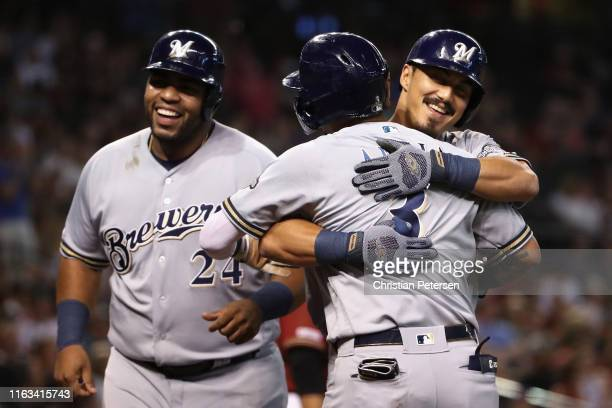 Tyler Saladino of the Milwaukee Brewers celebrates with Orlando Arcia and Jesus Aguilar after hitting a grand-slam home run against the Arizona...
