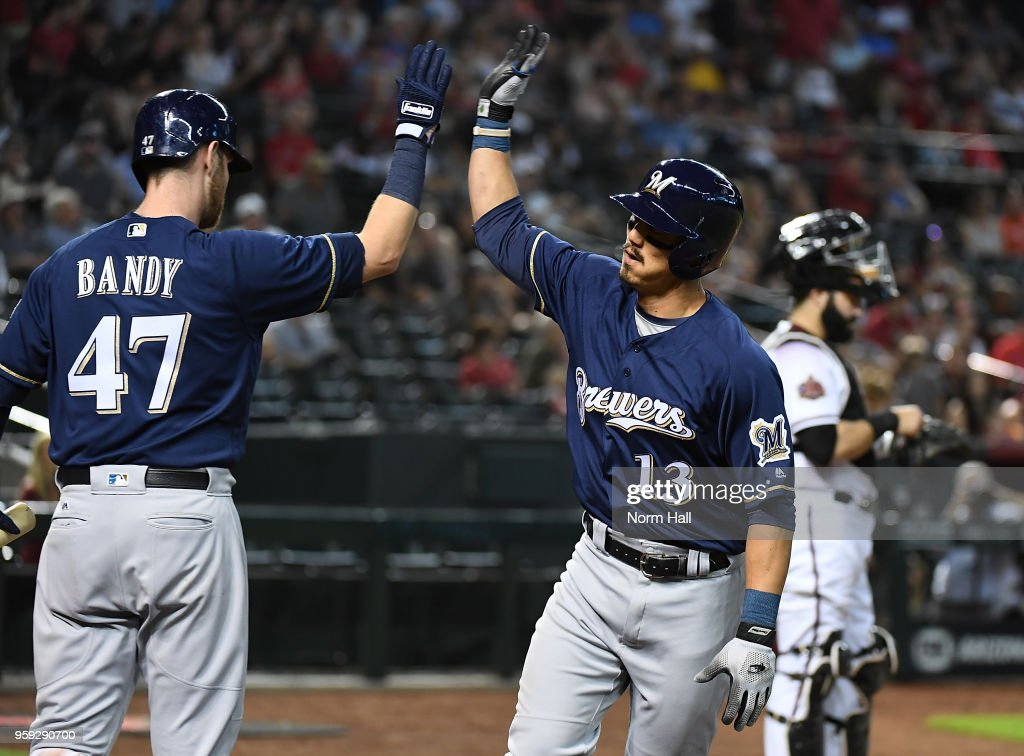 Tyler Saladino #13 of the Milwaukee Brewers celebrates with teammate Jett Bandy #47 after hitting a solo home run against the Arizona Diamondbacks during the fourth inning at Chase Field on May 16, 2018 in Phoenix, Arizona.