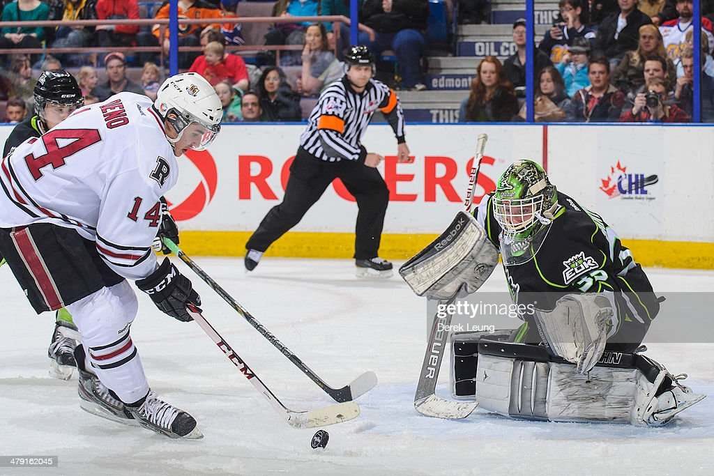 Tyler Santos #35 of the Edmonton Oil Kings eyes the shot of Rhyse Dieno #14 of the Red Deer Rebels during a WHL game at Rexall Place on March 16, 2014 in Edmonton, Alberta, Canada.