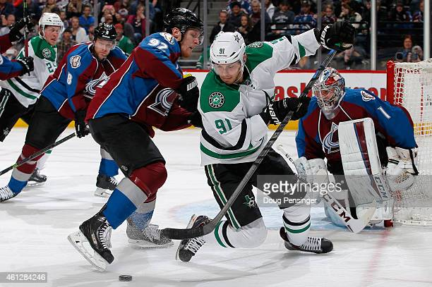 Tyler Seguin of the Dallas Stars controls the puck against Gabriel Landeskog of the Colorado Avalanche as goalie Semyon Varlamov of the Colorado...