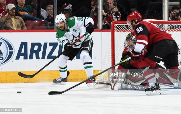 Tyler Seguin of the Dallas Stars passes the puck from behind the net as Jason Demers of the Arizona Coyotes defends during the second period of the...
