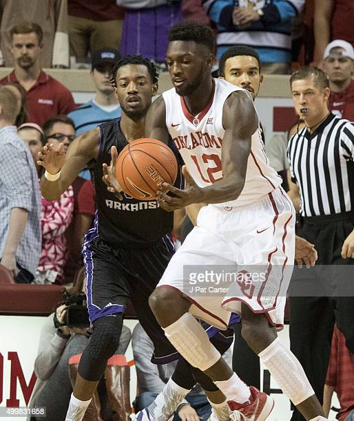 Tyler Simmons of the Central Arkansas Bears tries to steal the ball form Khadeem Lattin of the Oklahoma Sooners during the first quarter of a NCAA...