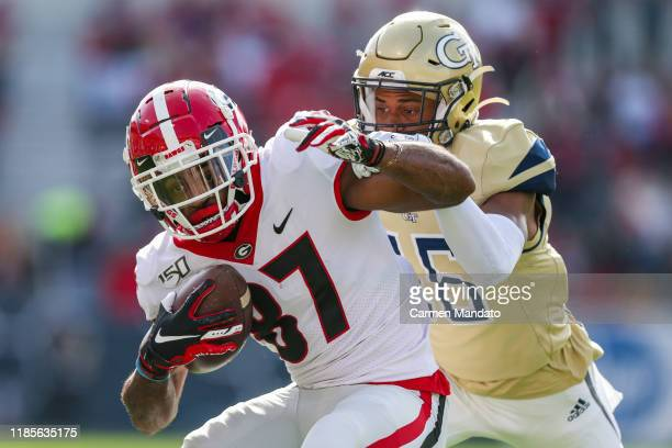 Tyler Simmons of the Georgia Bulldogs rushes ahead of defender Myles Sims of the Georgia Tech Yellow Jackets during the first half of the game at...