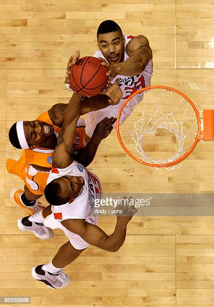 Tyler Smith of the Tennessee Volunteers drives to the hoop against James Anderson and Marshall Moses of the Oklahoma State Cowboys during the first...