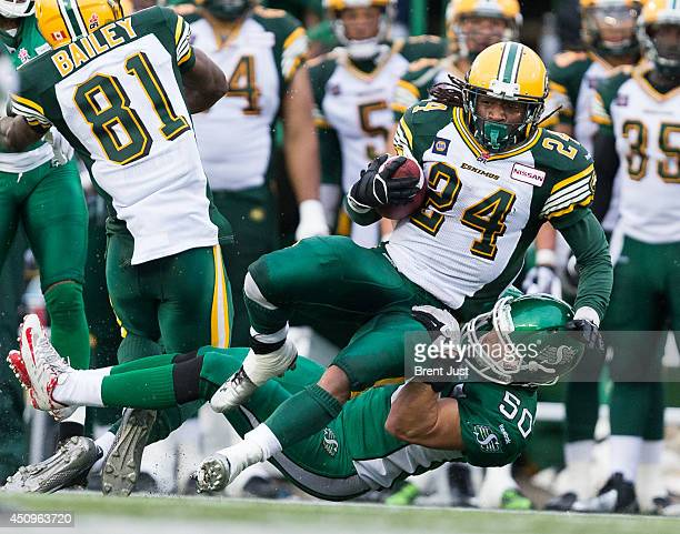 Tyler Thomas of the Edmonton Eskimos is tackled by Chad Kilgore of the Saskatchewan Roughriders during a preseason game between the Edmonton Eskimos...