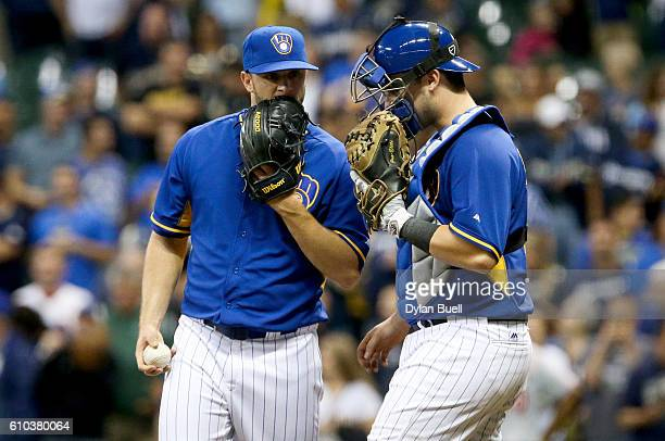 Tyler Thornburg of the Milwaukee Brewers chats with Andrew Susac in the ninth inning against the Cincinnati Reds at Miller Park on September 23 2016...