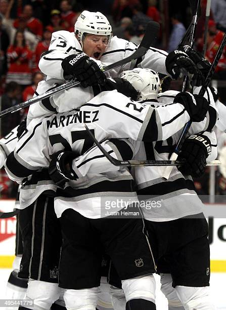 Tyler Toffoli of the Los Angeles Kings jumps on Alec Martinez and teammates after Martinez scored the game winning goal against Corey Crawford of the...