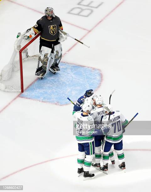 Tyler Toffoli of the Vancouver Canucks is congratulated by his teammates after scoring a goal as Robin Lehner of the Vegas Golden Knights reacts...