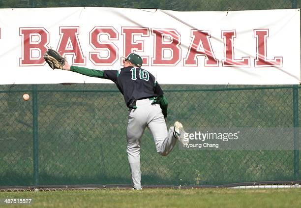 Tyler Tullis of Mountain Vista High School is chasing the ball hit by Max George of Regis Jesuit High School in the 1st inning of the game at Regis...