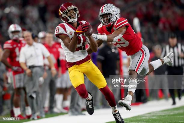 Tyler Vaughns of the USC Trojans pulls in a pass against Jeffrey Okudah of the Ohio State Buckeyes during the Goodyear Cotton Bowl Classic at ATT...