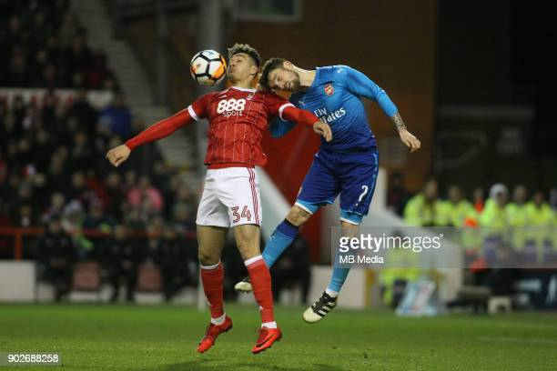 Tyler Walker beats Arsenal's Matthieu Debuchy to the ball during The Emirates FA Cup Third Round match between Nottingham Forest and Arsenal at City...