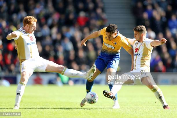 Tyler Walker of Mansfield Town is challenged by Dean Lewington and Jordan Houghton of Milton Keynes Dons during the Sky Bet League Two match between...