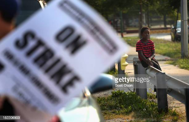 Tyler Whitaker watches from a distance as teachers from the Jose De Diego Community Academy where he is a third grade studennt walk the picket line...
