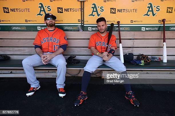 Tyler White and Jose Altuve of the Houston Astros sit in the dugout before the game against the Oakland Athletics at the Oakland Coliseum on Saturday...