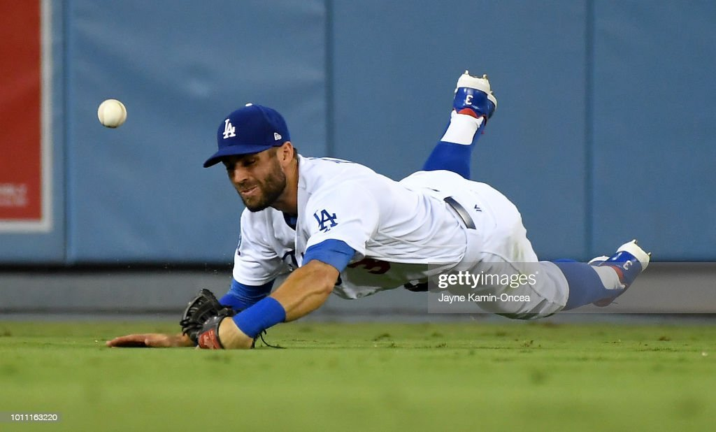 Tyler White #13 of the Houston Astros hits a two RBI double past a diving Chris Taylor #3 of the Los Angeles Dodgers in the sixth inning at Dodger Stadium on August 4, 2018 in Los Angeles, California.