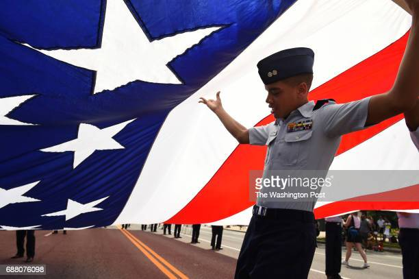 Tyler Whitsett a First Lieutenant cadet with the Civil Air Patrol United States Air Force Auxiliary helps to hold up a large American flag prior to...