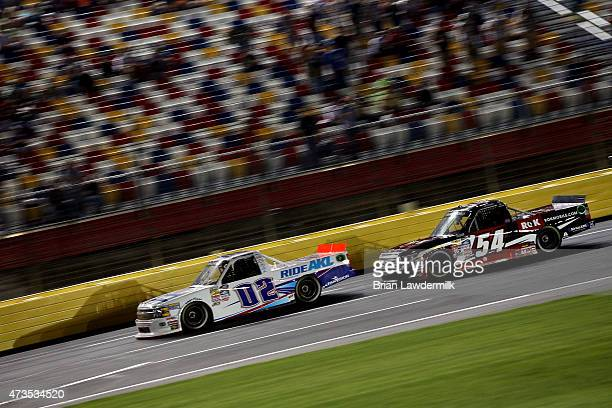 Tyler Young driver of the AKLInsrnceGrp/RandcoInd/YngsBldngSystms Chv races Justin Boston driver of the ROKMobilecom Toyota during the NASCAR Camping...