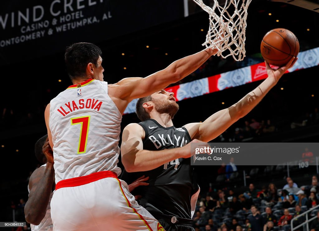 Tyler Zeller #44 of the Brooklyn Nets drives against Ersan Ilyasova #7 and Dewayne Dedmon #14 of the Atlanta Hawks at Philips Arena on January 12, 2018 in Atlanta, Georgia.