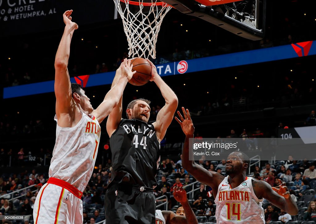 Tyler Zeller #44 of the Brooklyn Nets grabs a rebound against Ersan Ilyasova #7 and Dewayne Dedmon #14 of the Atlanta Hawks at Philips Arena on January 12, 2018 in Atlanta, Georgia.