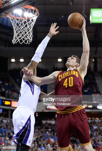 Tyler Zeller of the Cleveland Cavaliers slam dunks over Derrick Williams of the Sacramento Kings at Sleep Train Arena on January 12 2014 in...