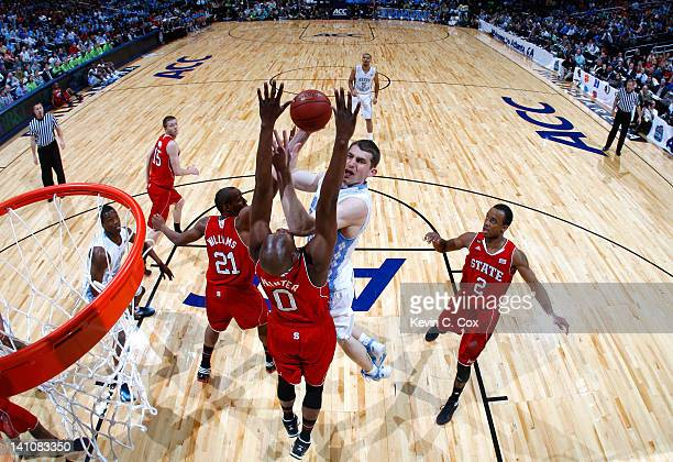 Tyler Zeller of the North Carolina Tar Heels shoots against CJ Williams and DeShawn Painter of the North Carolina State Wolfpack during the...