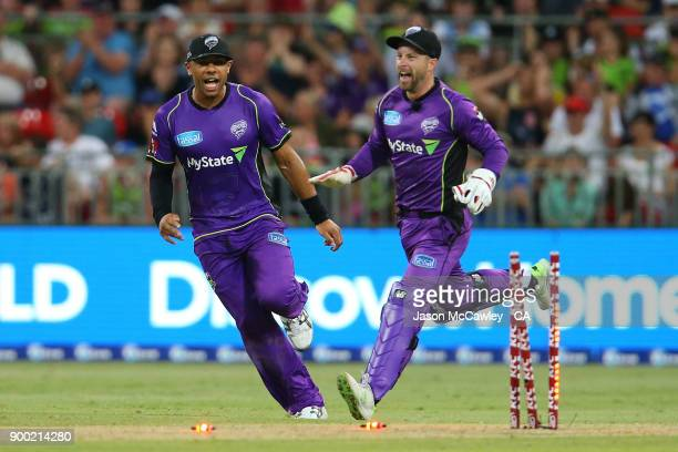 Tymal Mills of the Hurricanes and Matthew Wade celebrate the dismissal of Jos Butler of the Thunder during the Big Bash League match between the...